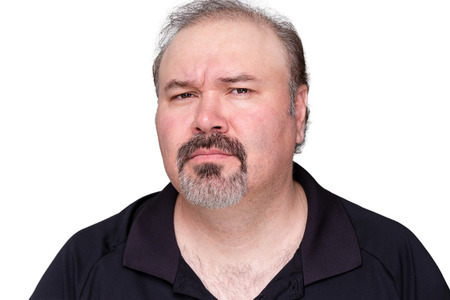 quizzical: Puzzled middle-aged man with a goatee frowning and looking at the camera with a look of distrust isolated on white