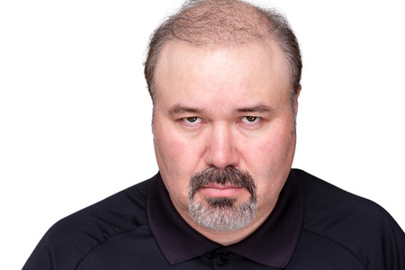 middle aged man: Dour angry middle-aged man glowering at the camera from under his brows, head and shoulders isolated on white Stock Photo