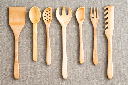 neatly: Row of assorted wooden kitchen utensils neatly arranged for size on a neutral beige cloth background viewed from above