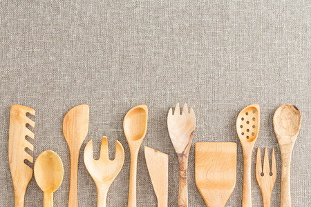 necessities: Border of wooden kitchen necessities with the heads of assorted utensils in a row along the bottom of the frame on a beige textile background with copyspace