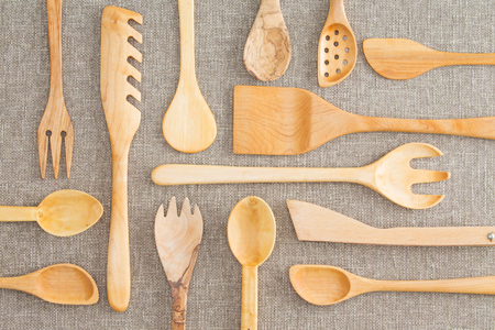Assorted set of wooden kitchen utensils in an overhead background view with spoons, ladles, pasta drainer, salad servers and draining spoon on a beige tablecloth photo