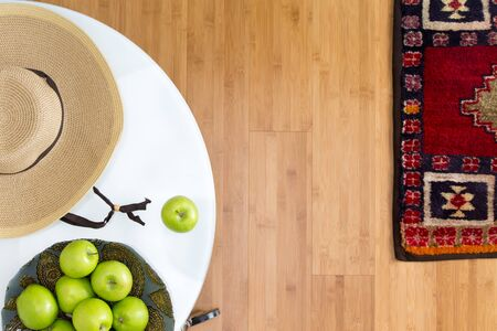 unprocessed: High Angle View of Healthy Fresh Green Apples and Brown Hat on Top of a White Table on the Wooden Floor with Carpet. Stock Photo