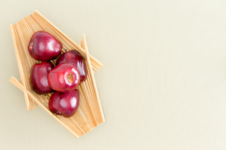 Healthy Fresh Red Apples on a Wooden Tray Placed on Top of a Light Green Table, Emphasizing Copy Space. Captured in High Angle View.