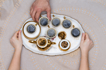 coffee table: Six Small Cups of Turkish Coffee on a Tray Hold by Hand on Top of a White Table in High Angle View. Stock Photo
