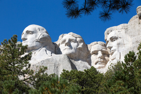 likeness: View up to the four Presidents faces - Lincoln, Roosevelt, Jefferson and Washington - sculpted into the granite rock on Mount Rushmore, South Dakota, USA framed by green pine trees against blue sky Editorial