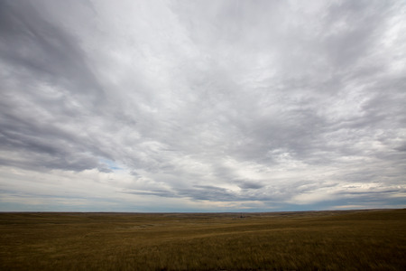 unbroken: Landscape view under a dramatic grey cloudy sky of the vast open plains and prairies of North Dakota, America stretching as flat unbroken fields as far as the eye can see
