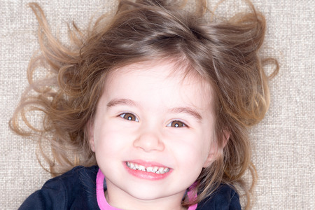 sincere girl: Headshot of young three year old girl lying on a carpet with tousled hair grinning up at the camera with a happy expression