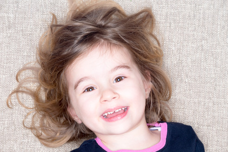 spontaneous expression: Pretty vivacious three year old little girl lying on a carpet with her hair flying around her face smiling happily up at the camera with a joyful expression