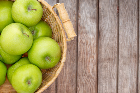 produce: Wicker basket of crisp fresh green apples displayed on a wooden picnic table or at a farmers market for fresh produce direct from the farm, overhead view with copyspace