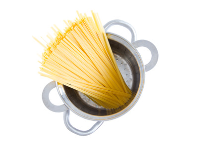 durum wheat semolina: Overhead view of a bundle of dried fettuccine pasta standing upright in a pot ready for boiling for an Italian pasta recipe, isolated on white