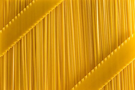 crimp: Dried uncooked fettuccini pasta and lasagne background textue with a decorative arrangement of the lasagne as diagonal stripes over the fettuccine, overhead view