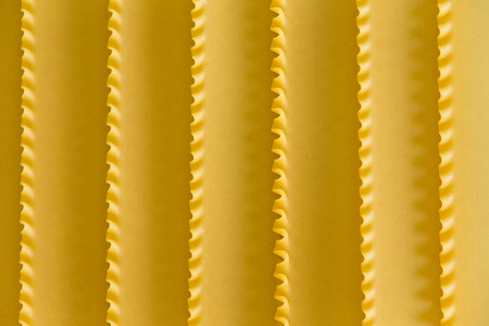 crimp: Organic dried durum wheat semolina lasagne background texture with a decorative parallel pattern formed by the crimped edges of the sheets