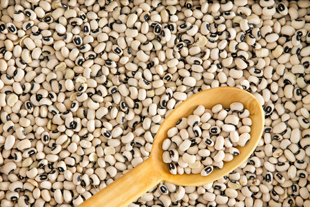 vigna: Full frame background of dried black-eyed peas or beans, Vigna unguiculata, or cowpea, grown as a staple nutritional crop, as animal fodder and to enrich soil, with a spoonful in a wooden spoon
