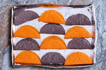 american cuisine: Crunchy tortillas, a traditional flatbread made with cornflour or maize popular in Latin American cuisine, waiting to be heated in the oven arranged in a colorfu alternating pattern in a baking tray