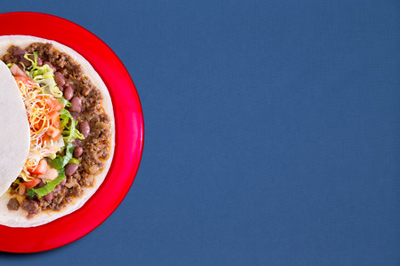 maize: Soft taco with savory filling and vegetables served on a red plate over a blue background with copyspace, overhead view