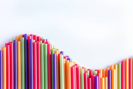 come up to: What goes up must come down concept with a wave form arrangement of colorful plastic drinking straws over a light grey background with copyspace