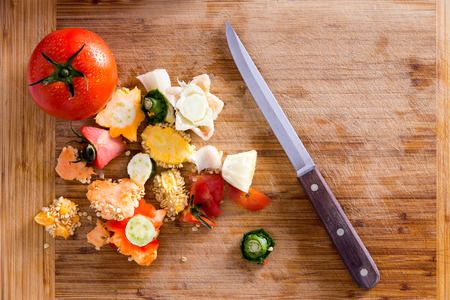 wastes: Organic Wastes from Veggies and Spices, Can be Used to Compost Garden Soil, on Top of Wooden Chopping Board with Kitchen Knife. Captured in High Angle View.