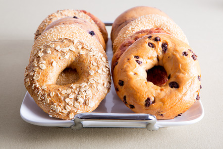 deliciously: Close up Deliciously Baked Bagel Breads for Office Snacks Piled on a White Tray and Served on the Table. Stock Photo