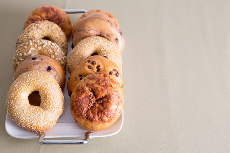 Fresh Bagel Breads, Good for After Office Meeting Snacks, Prepared on a White Tray Placed on a Table with Copy Space.