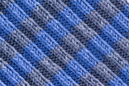 ridged: Background texture of handmade crochet work in blue and grey with a wavy repeating ridged pattern with weave, yarn and fiber detail and diagonal ridged lines, full frame close up from above Stock Photo