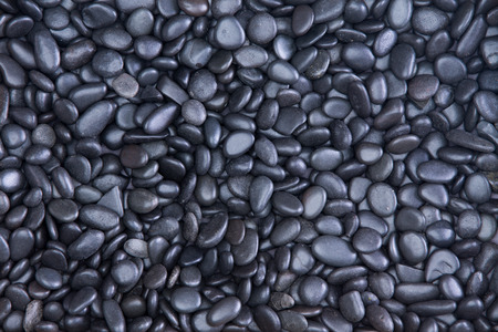 Background texture of small smooth waterworn black pebbles or stones for use in decor and garden landscaping, full frame close up view from above