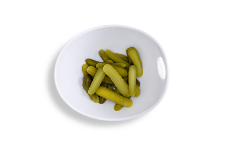 centered: Close up Pickles for Your Taste Buds on a Contemporary Glossy Bowl Isolated on a White Background. Captured in High Angle View. Stock Photo