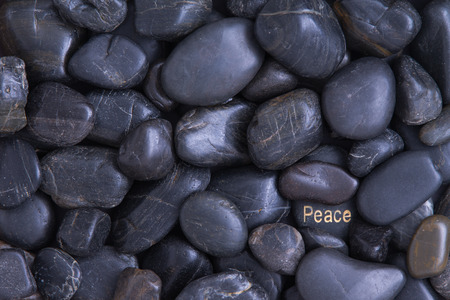Smooth waterworn smooth black pebble full frame background with a Peace theme with one pebble in the lower right corner bearing the word in white