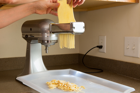 feeding through: Chef preparing homemade fettuccine pasta feeding the rolled sheets of dough through the cutting machine in the corner of a kitchen, close up view of the dough and appliance