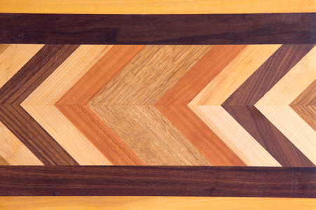 Decorative marquetry on a cutting board with inlaid wood of different colors forming a chevron pattern inside a black linear border, full frame background Stock Photo