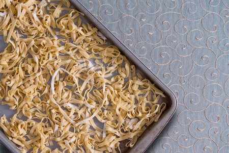 curlicues: Overhead view of fresh homemade fettuccine pasta noodles drying on a metal tray placed on a decorative tablecloth with swirling curlicues and copyspace