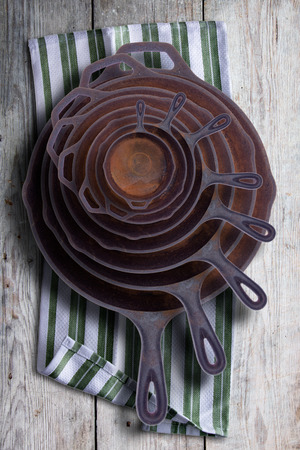 cast iron: Collection of round rusty cast iron frying pans in diminishing sizes stacked one inside the other, viewed from above on a rustic napkin on an old wooden table