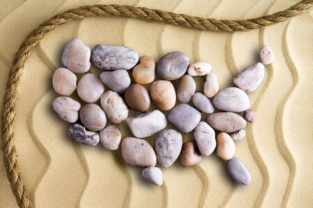 Pebbles arranged in the shape of a map of the United Sates of America on decorative beach sand with wavy lines in an undulating pattern with a rope border in a nautical theme Stock Photo