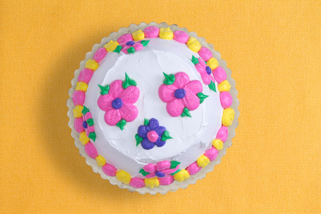 mouth cloth: Top view of a decorative iced homemade cake with colorful pink and blue flowers surrounded with a yellow and pink alternating border, served uncut on a yellow background with copyspace Stock Photo