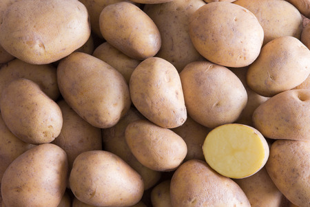 lower section: Full Frame of Whole Golden Potatoes with One Cut Half Section in Lower Right Corner Stock Photo