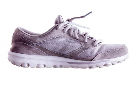 pliable: Lightly used grey sports shoe or trainer with laces in a close up side view isolated on white