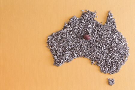 silvery: Conceptual map outline of Australia and Tasmania formed from an arrangement of silvery stone chips and fragments on a yellow textile background with copyspace Stock Photo