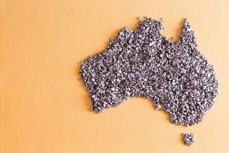 silvery: Conceptual map of Australia formed of small silvery stones on a yellow textile with weave detail and copyspace
