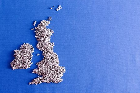 conceptual map: Mapa conceptual del Reino Unido y Rep�blica de Irlanda formado de piedras plateadas decorativos sobre un tejido de color azul con copyspace y el detalle de la armadura Foto de archivo