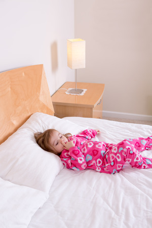 wakening: Adorable small girl in pink pajamas lying resting on a big king size bed picking her nose as she awakens from her daily nap