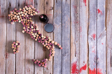 Artistic conceptual map of Italy, Sardinia and Sicily made of old red and white wine bottle corks on an old rustic wooden table with a glass and bottle of red wine alongside