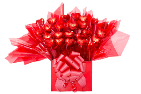 cellophane: Colorful red gift of heart-shaped chocolate flowers in decorative cellophane tied with a bow for a loved one or sweetheart on Valentines Day, anniversary or Mothers Day, isolated on white Stock Photo