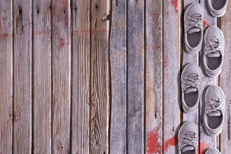 floorboards: Shoe border with a double row of worn trainers or sneakers arranged as though walking on a textured hardwood background of old floorboards with wood grain, red paint remnants and copyspace