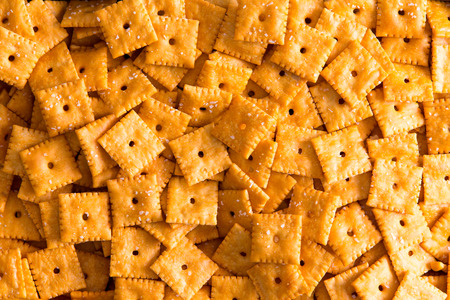 full of holes: Texture of square cheese crackers with central holes arranged in a layer viewed close up full frame from above Stock Photo