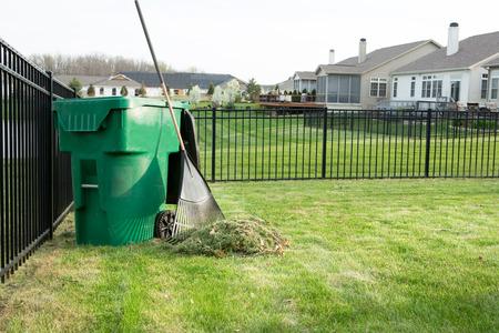 organic waste: Rastrillo de recortes de c�sped en un aseado lujo urbanizaci�n suburbana con un mont�n de corte de c�sped junto a un rastrillo apoyado en un cubo de pl�stico verde para el compostaje de residuos org�nicos Foto de archivo