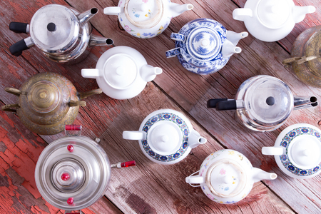 orientated: Army of a assorted metal and ceramic Turkish and conventional tea pots arranged in regimental rows all facing the same direction viewed from above on a rustic wood background Stock Photo