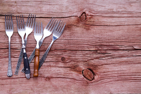 prongs: Random pile of assorted rustic forks arranged on the side of a rustic wooden table with copyspace in a concept of country cuisine, overhead view Stock Photo