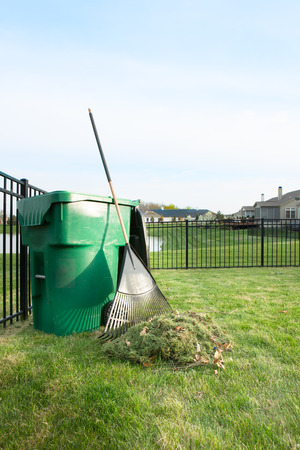 Yard maintenance in spring cleaning the lawn and raking up grass clippings after mowing with a pile of grass and rake leaning on a plastic bin for composting Stock Photo