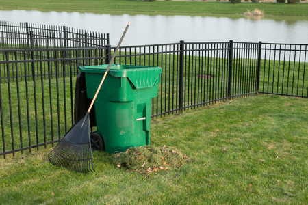 composting: Yard maintenance in spring with a fresh heap of grass clippings and a rake leaning on a green plastic bin for composting organic waste on a neat lawn with wrought iron fence above a lake