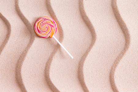 sucker: Nothing tastes crunchier than a sandy lollipop at the seaside on a summer vacation with a twirled round sucker on white beach sand with a decorative wavy pattern and copy space