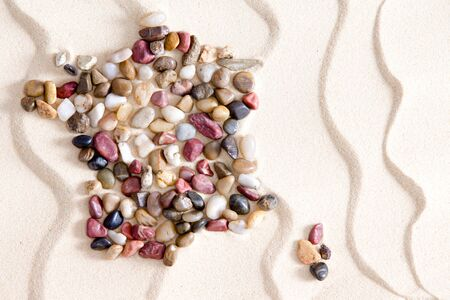 tumbled: Conceptual map of France and Corsica formed of colorful waterwashed pebbles of quartzite, agate, jasper, and dolomite on white bach sand with an undulating wavy pattern